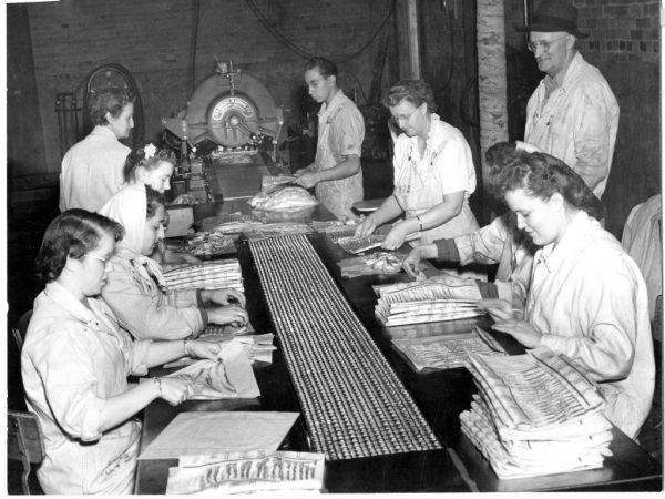 Women and a young man packaging bacon, with a man standing, taken inside the Swift meatpacking plant. Photo obtained from Weber State University Special Collections