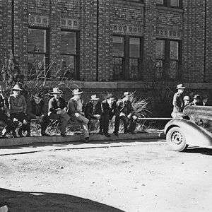 13 men wearing hats and long sleeves sitting on a rail lining the parking lot in front of the Exchange Building. Thank you to Don Strack for generously sharing this photo, part of his extensive gallery. Ogden Union Stockyards.