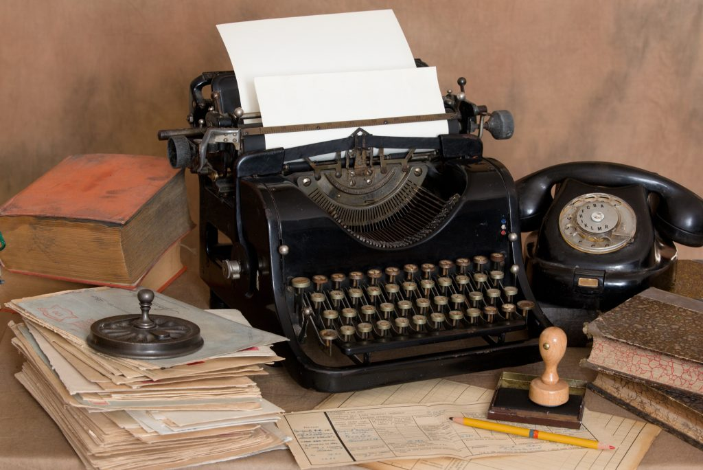 Stock photo of a vintage office typewriter, stamp, telephone and papers with a paper weight on top