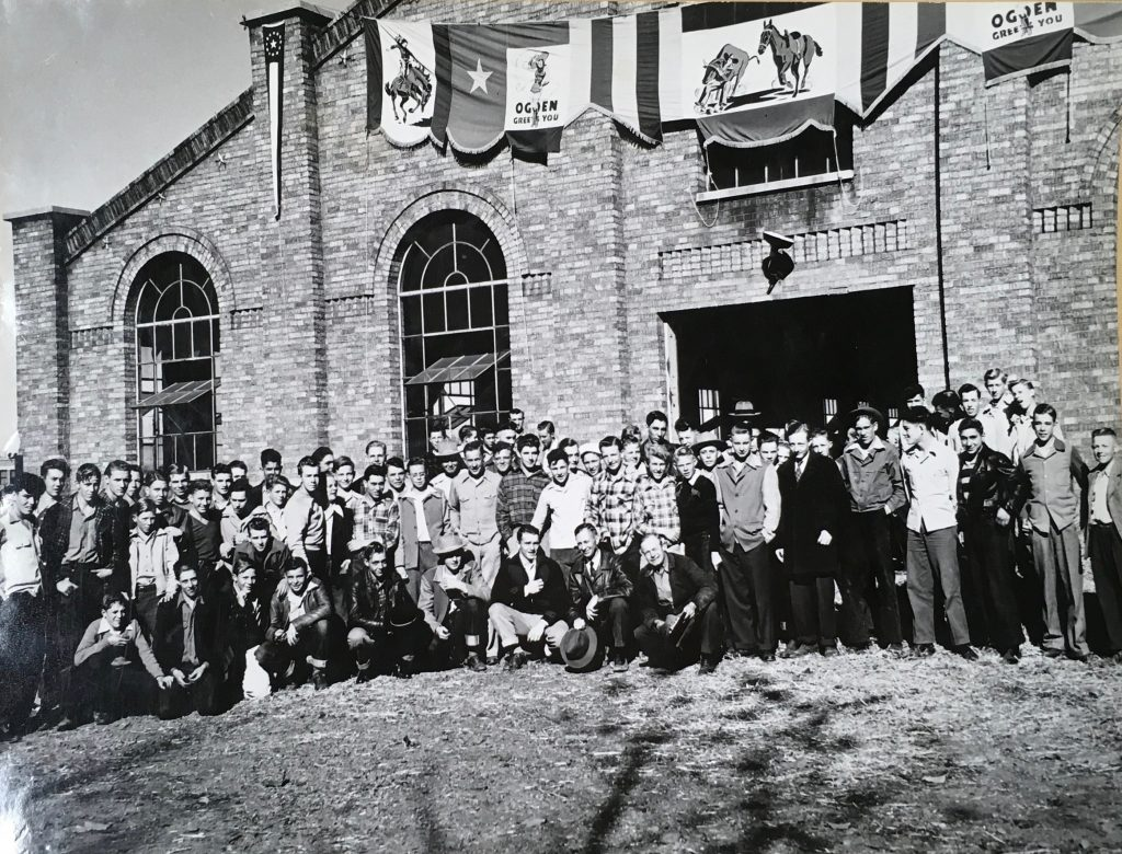 "Bear River High school future farmers visit the 1945 show. Photo of teenage boys wearing long sleeves and some with hats. Standing in front of a building. The coliseum? The building is draped with flags that say ""Ogden greets you."" with the whoopee girl and cowboys. Special Collections Department, Stewart Library, Weber State University"