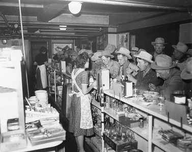 Two waitresses wearing dresses and floral aprons stand behind counter while men wearing cowboy hats eat at the bar. Behind the counter is a box of empty Nehi glass bottles. Possibly the Stockman's Cafe, or the restaurant in the basement of the Exchange Building. Thank you to Don Strack for generously sharing this photo, part of his extensive gallery.